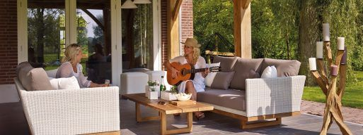 Two woman sit on their patio furniture on a sunny day while one of them plays the guitar.