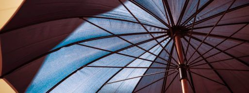 Close up image of the underside of a tan and black patio umbrella.