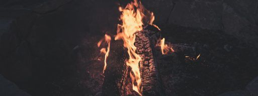 A wood fire in a fire pit burns warmly in the night.