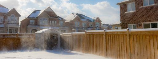 Snowy residential backyard surrounded by five foot fences and homes in the background