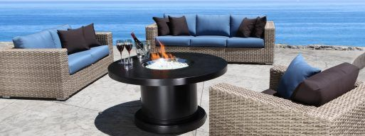 A beautiful fire table sits next to the waterfront.